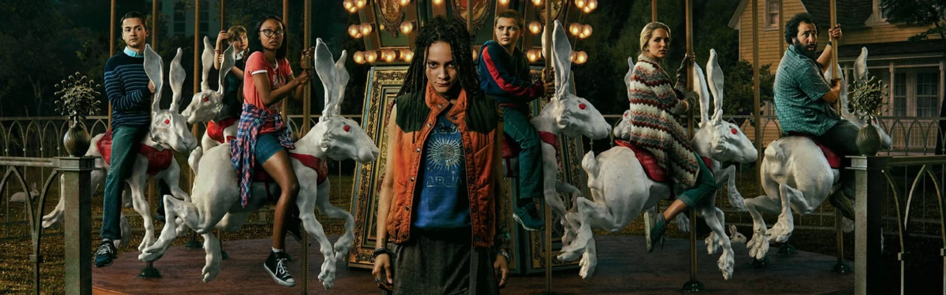 A girl stands in front of a carousel with people riding rabbits