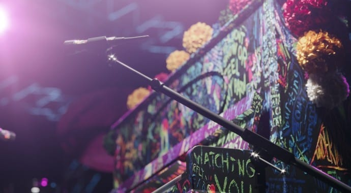 A microphone next to a colorful piano covered with chalk words
