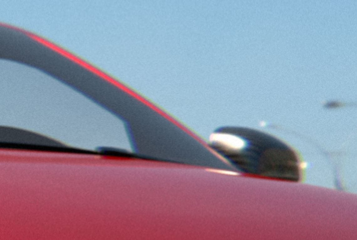 a red car's wing mirror with chromatic aberration