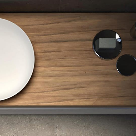 A top-down view of a white oval sink with a wood surround